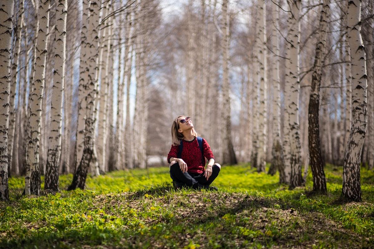 woman sitting outside in aspen trees
